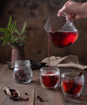Eine hand gießt roten rosentee aus einer glasteekanne in klare tassen auf einem braunen holztisch. vorderansicht