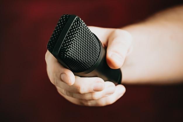Eine hand griff nach einem mikrofon über rot