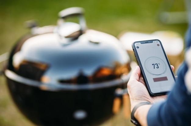 Eine hand hält ein digitales thermometer für ein gegrilltes steak mit einer anzeige auf dem bildschirm. temperaturzahlen. nahansicht . platz kopieren.