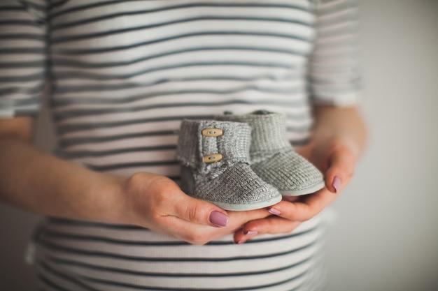 Eine hand hält ein paar kleine schuhe. es ist ein schuh für kleinkinder. mutter und baby thema. schwangere frau. glück