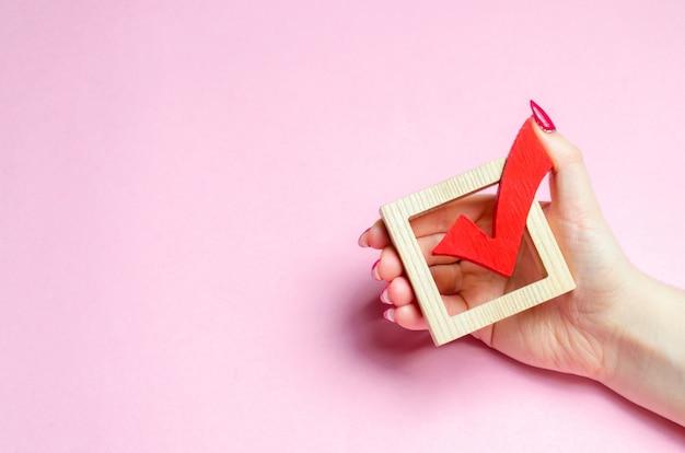 Eine hand hält ein rotes häkchen, um abzustimmen