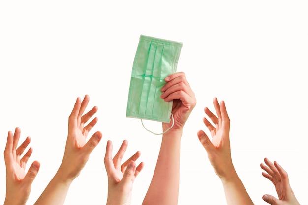 Eine hand hält eine gesichtsmaske mit vielen händen, die versuchen, sie zu ergreifen