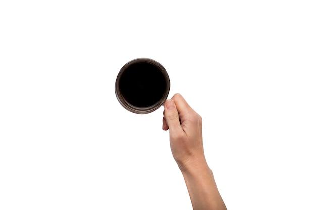 Eine hand hält eine tasse mit heißem kaffee auf einem weißen isolierten hintergrund. frühstückskonzept mit kaffee oder tee. guten morgen, nacht, schlaflosigkeit. flache lage, draufsicht