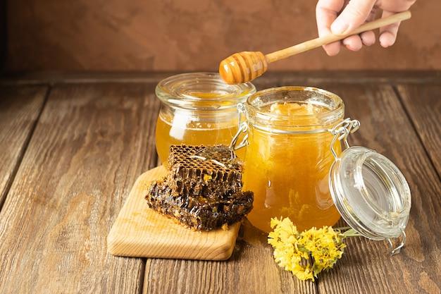 Eine hand hält einen holzlöffel, auf dem honig fließt. banken von frischem goldenen blumenhonig auf holz auf dem tisch