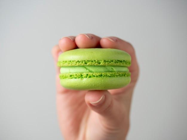 Eine hand hält einen süßen, köstlichen mandelkeks von grüner farbe auf weißem hintergrund. französisches dessert