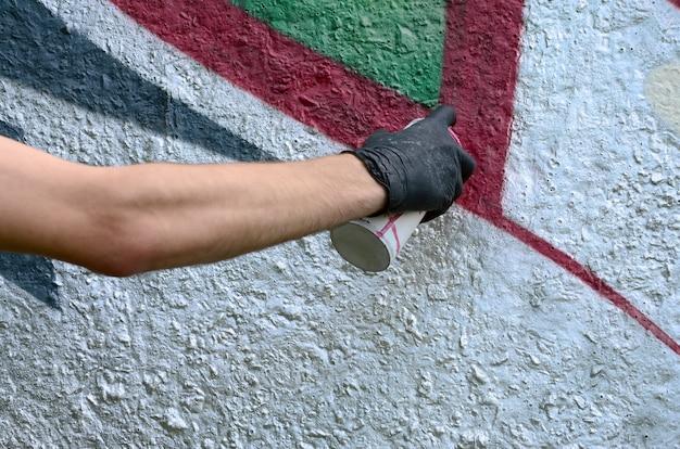 Eine hand in den schwarzen handschuhen malt graffiti auf einer betonmauer. konzept des illegalen vandalismus. straßenkunst