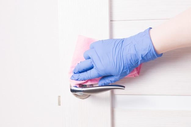 Eine hand in einem blauen einweg-gummihandschuh wischt einen türknauf mit einem rosa lappen ab und reinigt und desinfiziert oberflächen