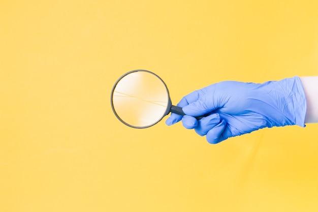 Eine hand in einem blauen einweghandschuh hält eine lupe