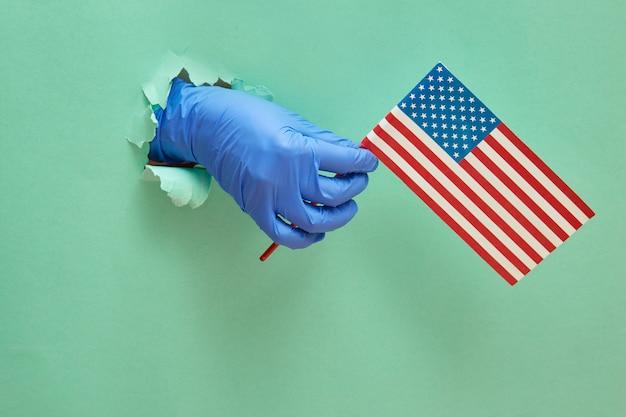 Eine hand in einem blauen nitrilschutzhandschuh hält die amerikanische flagge. der moderne trend ist ein loch im papier mit kopierraum.