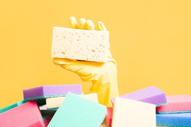 Eine hand in einem gelben gummihandschuh hält einen schwamm zum abwaschen und reinigen, eine hand ragt aus einem schwammhaufen auf gelber oberfläche