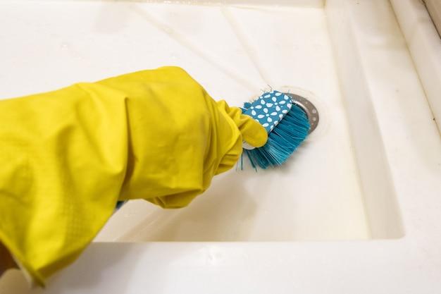 Eine hand in einem gelben handschuh reinigt das waschbecken im badezimmer mit einer blauen bürste am griff. das konzept der hausaufgaben, desinfektion