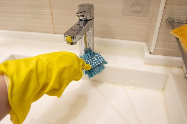 Eine hand in einem gelben handschuh reinigt das waschbecken mit einer blauen bürste am griff. das konzept der hausaufgaben, desinfektion. Premium Fotos