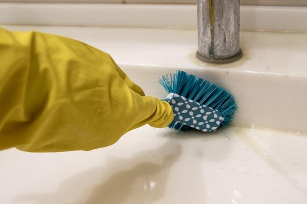Eine hand in einem gelben handschuh reinigt das waschbecken mit einer blauen bürste am griff und reinigt das badezimmer. das konzept der hausaufgaben, desinfektion