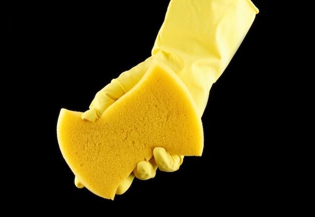 Eine hand in einem gelben reinigungshandschuh hält einen schwamm