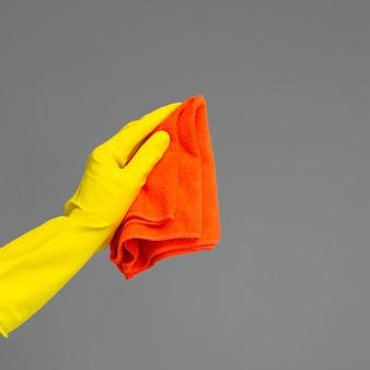 Eine hand in einem gummihandschuh hält einen hellen mikrofaserstaubtuch auf einer neutralen stelle.