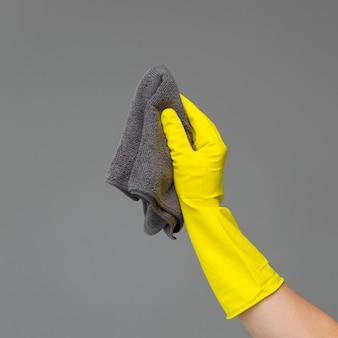 Eine hand in einem gummihandschuh hält einen hellen mikrofaserstaubtuch