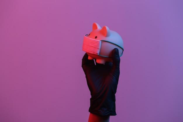 Eine hand in einem handschuh hält ein sparschwein mit einer medizinischen maske rotblaues neon-gradientenlicht
