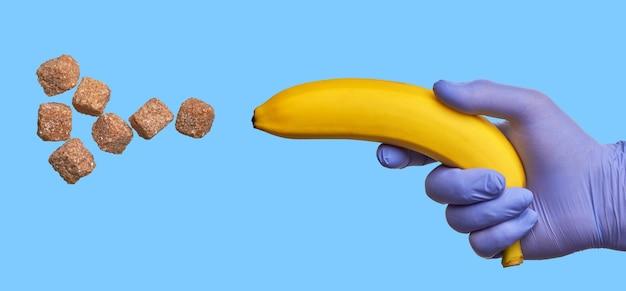 Eine hand in einem latexhandschuh hält eine banane, die zucker schießt. hoher gehalt an schnellen kohlenhydraten in süßen früchten. diabetiker-diät-konzept