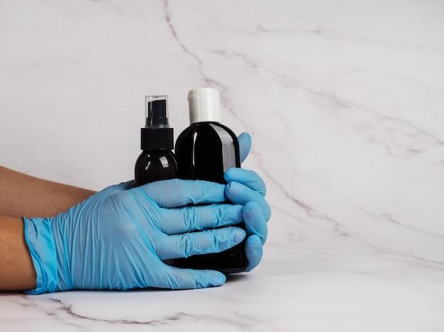 Eine hand in einem medizinischen handschuh hält ein glas sahne