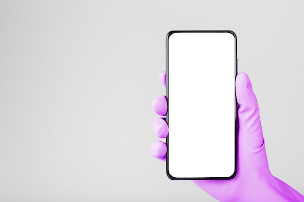 Eine hand in einem rosa medizinischen handschuh hält ein schwarzes smartphone mit einem leeren weißen bildschirm und isoliert auf einer grauen oberfläche