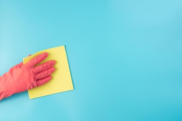 Eine hand in einem roten handschuh wischt den staub mit einem gelben lappen von der wand.