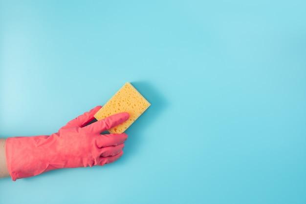 Eine hand in einem roten handschuh wischt die wand mit einem gelben schwamm von staub ab.