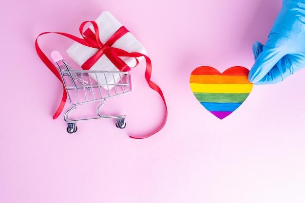 Eine hand in einem schützenden blauen handschuh hält ein regenbogenpapierherz neben einem geschenk in einem einkaufswagen auf einem rosa hintergrund. sicheres urlaubsgrußkonzept. sicheres online-shopping-konzept. lgbtql-konzept