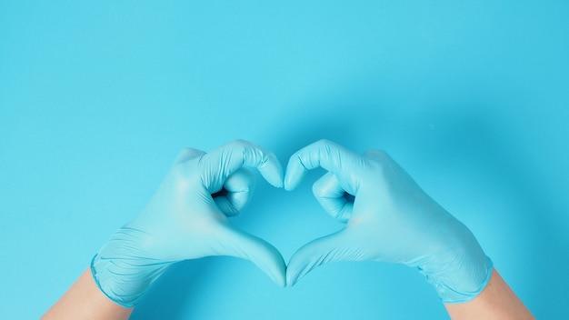 Eine hand macht ein miniherz-handzeichen und trägt chirurgische handschuhe oder latexhandschuhe auf blauem hintergrund.