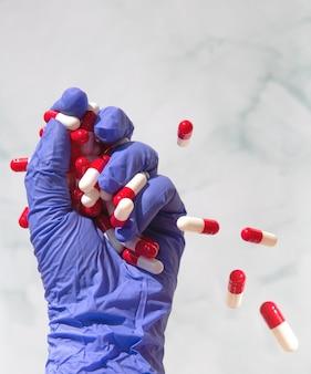 Eine hand mit blauen latexhandschuhen greift nach einer hand voller medikamente, kapseln für vitamine, drogen, medikamente. gesundheit, geschäftskonzept