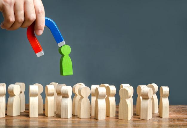 Eine hand mit einem magneten zieht eine grüne menschliche figur aus der großen menschenmenge heraus. neue arbeitskräfte einstellen