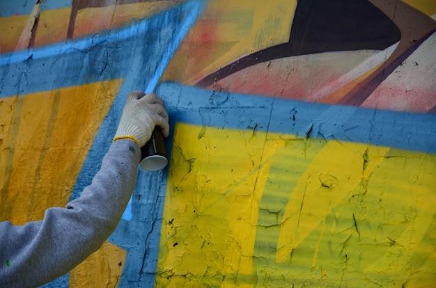 Eine hand mit einer spraydose, die ein neues graffiti an die wand zeichnet