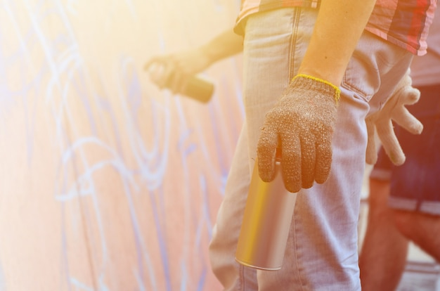 Eine hand mit einer spraydose, die ein neues graffiti an die wand zieht.