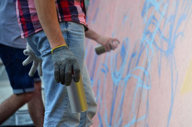 Eine hand mit einer spraydose, die ein neues graffiti an die wand zieht