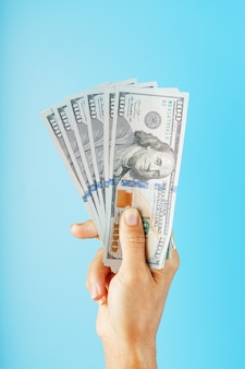 Eine hand mit einhundert dollarnoten auf blau.