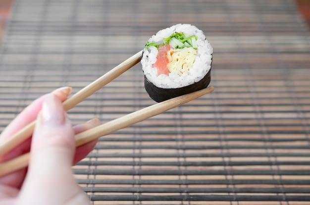 Eine hand mit stäbchen, die eine sushi-rolle halten