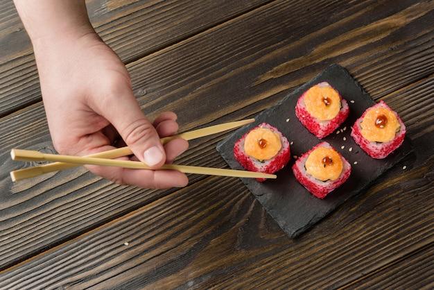 Eine hand mit stäbchen nimmt eine rolle aus einer schüssel. traditionelles japanisches essen.