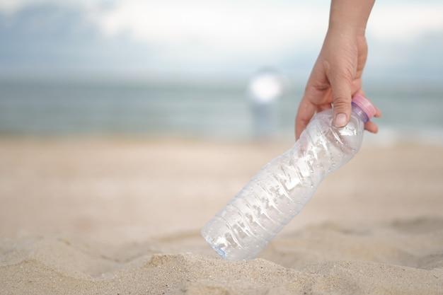 Eine hand nimmt die plastikflasche vom strand