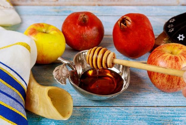 Eine hand nimmt eine mit honig für die apfelscheibe und granatapfelfeiertag von rosh ha shana
