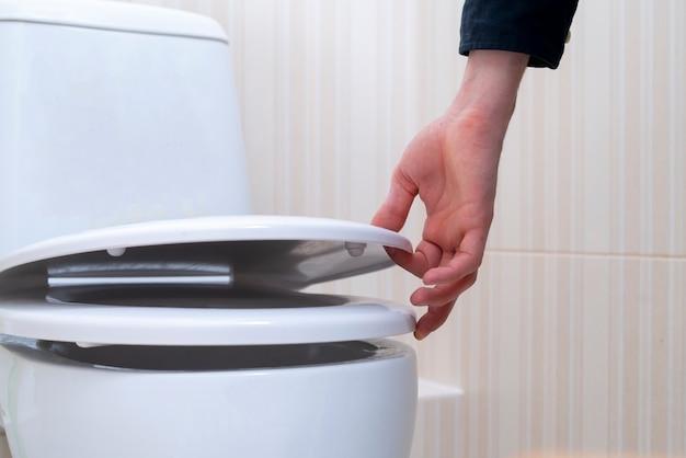 Eine hand öffnet den toilettendeckel, haushaltshygiene