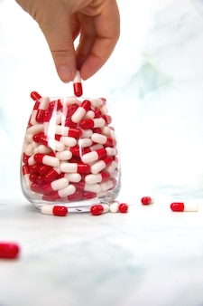 Eine hand packende hand voller medikamente, kapseln für vitamine, medikamente, medikamente. hintergrundkopieplatz des gesundheits-, geschäftskonzepthintergrunds