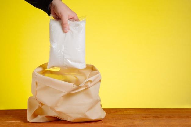 Eine hand steckt zucker in eine einkaufstasche. das konzept des kaufs und der lieferung von produkten.