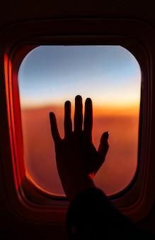 Eine hand über das fenster des flugzeugs. reisekonzept.