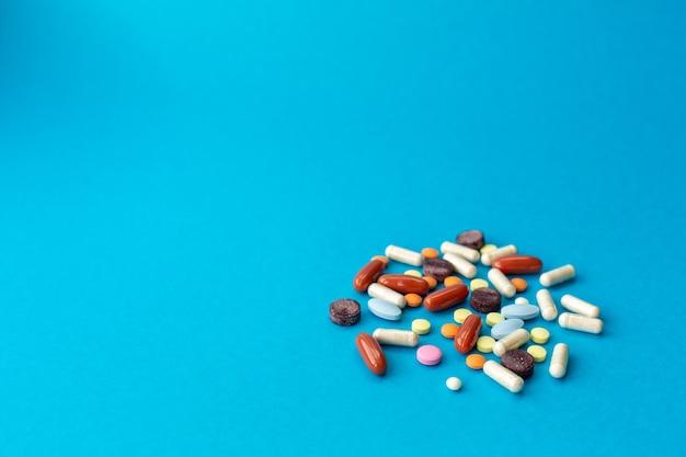Eine handvoll farbiger pillen verschüttete sich auf einem blauen tisch. medizinisches konzept.