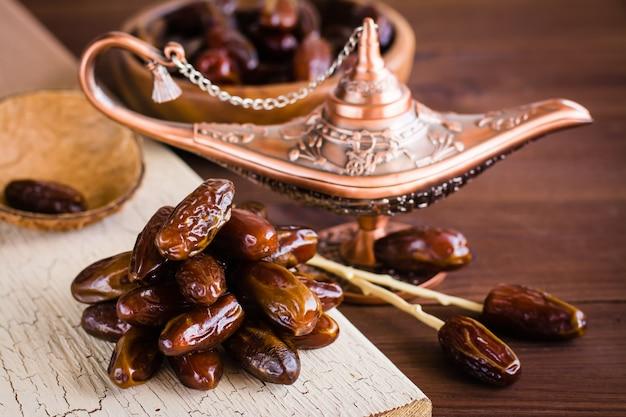 Eine handvoll getrocknete dattelfrüchte auf einer lampe von aladdin. frische orientalische süßigkeiten.