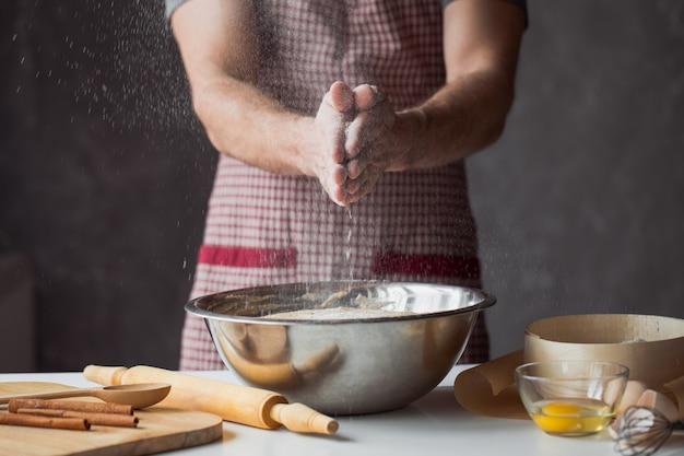 Eine handvoll mehl mit ei auf einer rustikalen küche. an die wand der männerhände kneten sie den teig