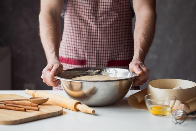 Eine handvoll mehl mit ei auf einer rustikalen küche. kneten sie den teig gegen den tisch der männerhände