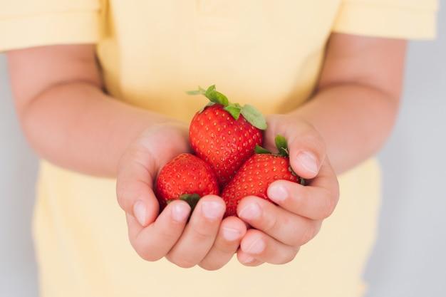 Eine handvoll reifer erdbeeren in den händen eines kindes, hände in nahaufnahme.