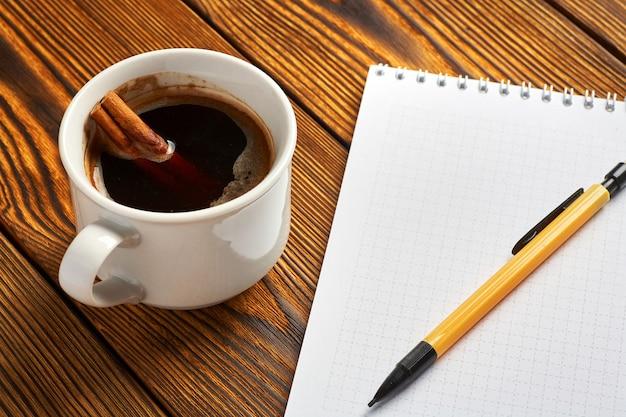 Eine haufen zimt mit einem seil, einer tasse kaffee und einem notizbuch gestrickt