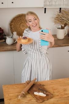 Eine hausfrau oder ein konditor macht ein selfie mit dessert. lebensmittelblog. kochkurse. bloggerin