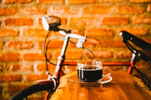 Eine heiße tasse kaffee auf holztisch in der kaffeestube